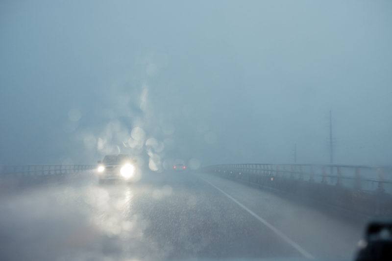 Photograph of a rainy drive across a bridge with other automobiles passing.