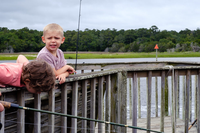 Two young brother fishing on a dock. One talking to the other that is looking down into the water for a fish.