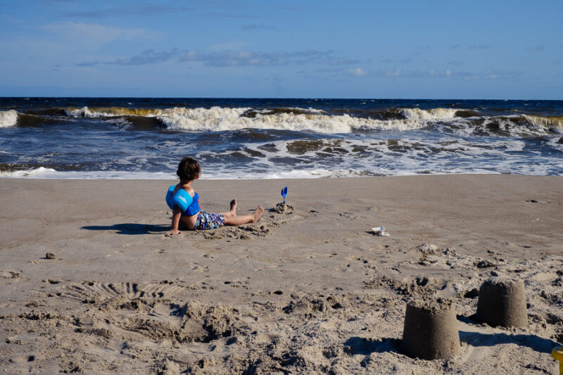 A toddler taking a break from playing in the sand on the beach to take in the size of the ocean.