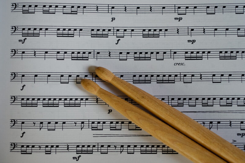 Drum sticks laying on sheet music.