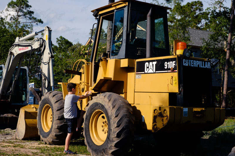 A boy climbing up on to a Caterpillar front end loader.