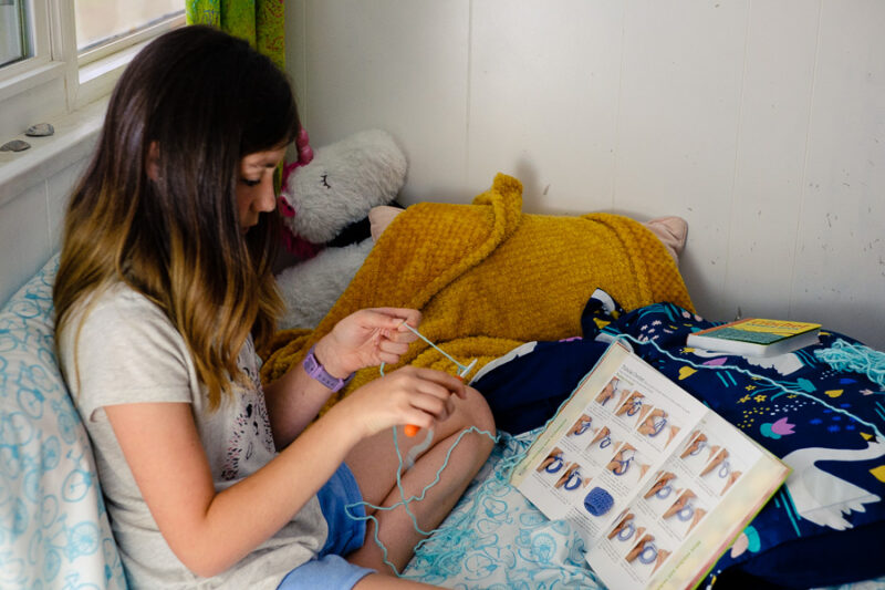 A girl learning to crochet from a book.