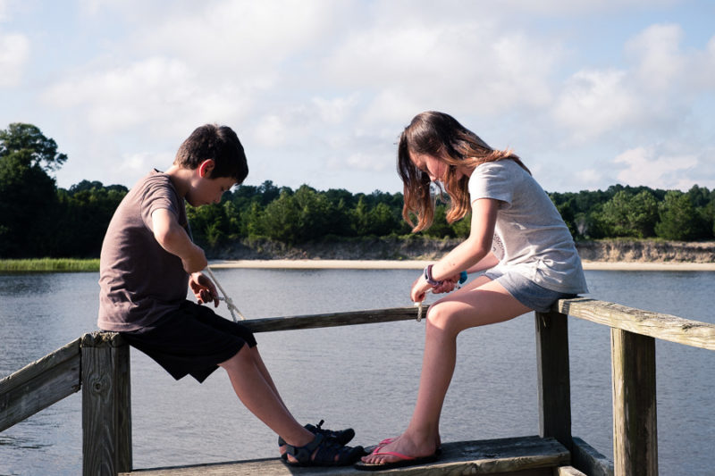 Kids practicing knot tying on a dock by the waterway