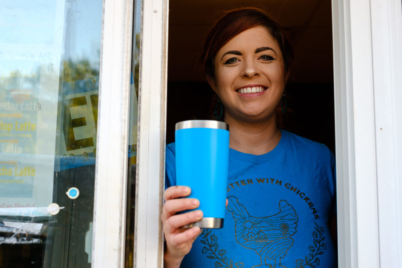 Smiling barista handing a cup of coffee through a drive-through window