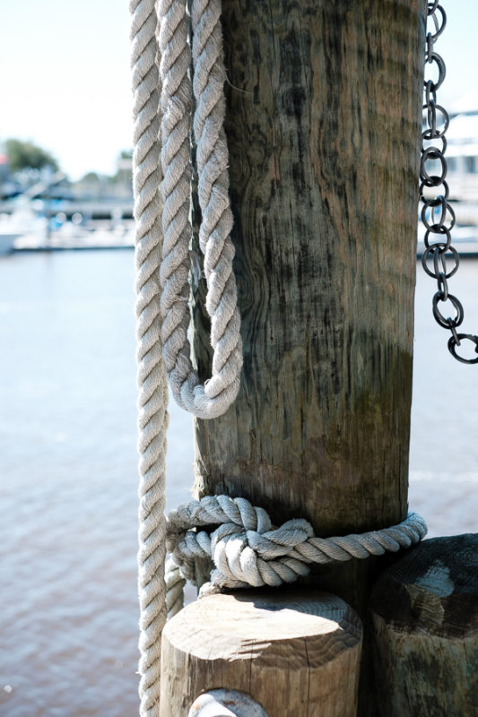 Ropes used to secure ferry hanging on and dock piling