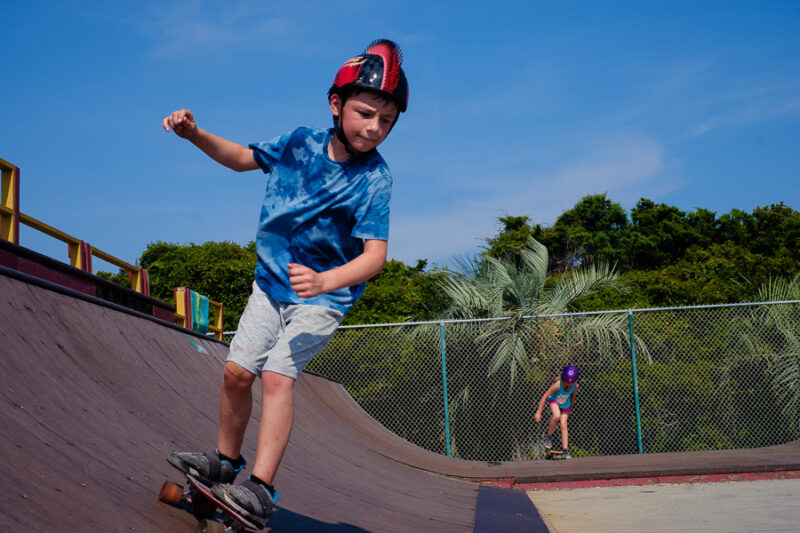 Two children play on in a skateboard park and a sunny day.