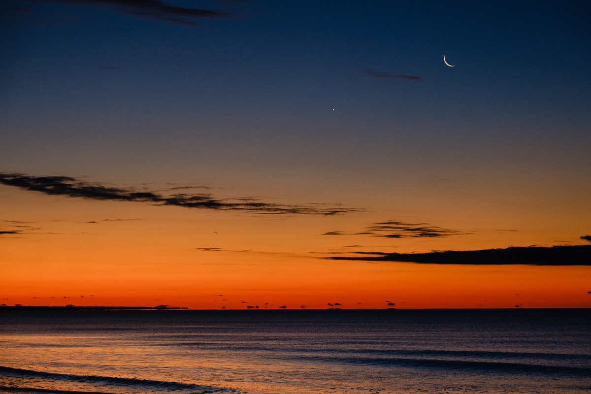 Photo looking over the ocean with Venus and the Moon above an orange sky just before sunrise.