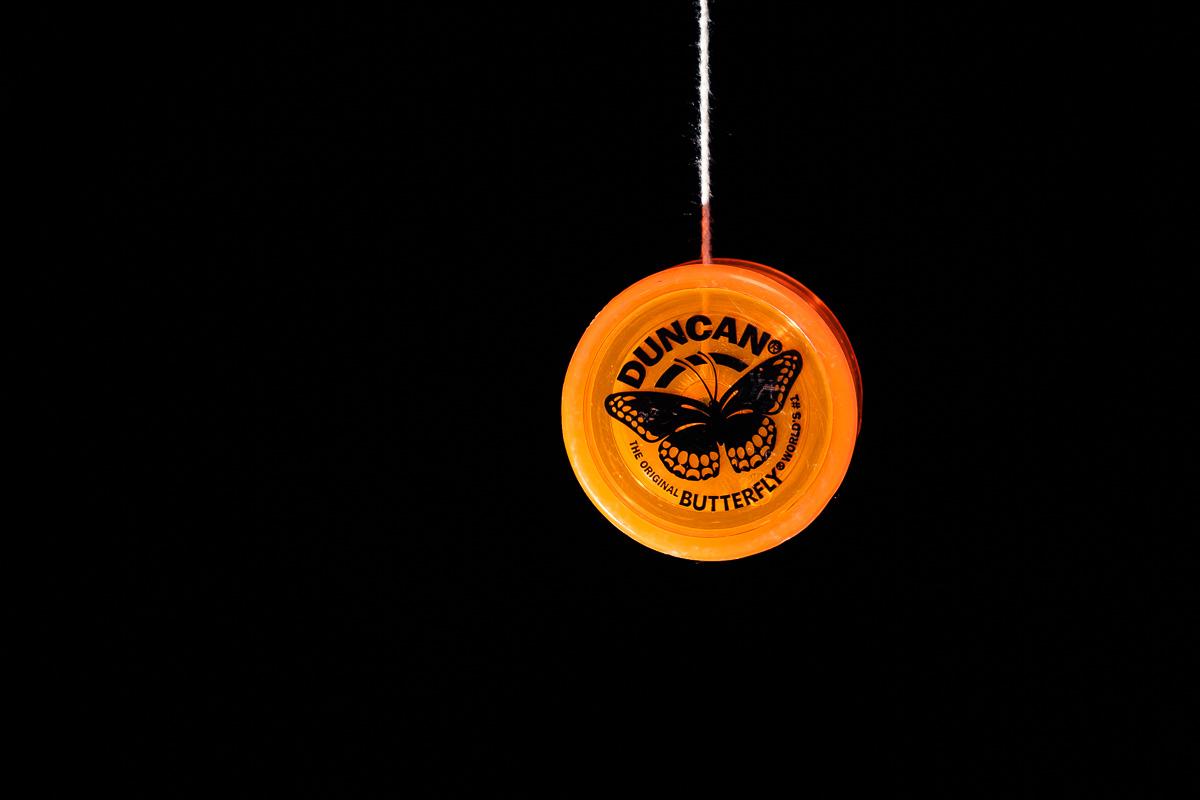 An orange Duncan Butterfly yo-yo on a dark background